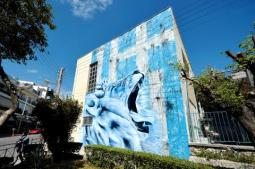 A giant lion roars before a frayed Greek flag on a graffiti by BANE on a wall of a primary school in the Athens suburb of Nikaia on this picture taken at the end of April.Jun 15, 2014, afp